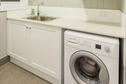 Small Laundry idea with custom made cabinet and benchtop over washing machine